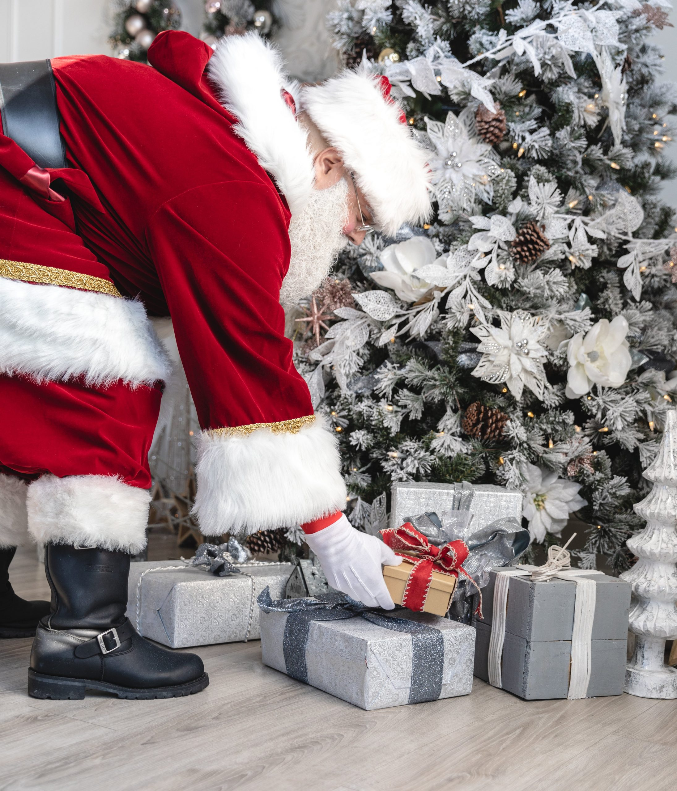 Image of santa placing gifts under a tree
